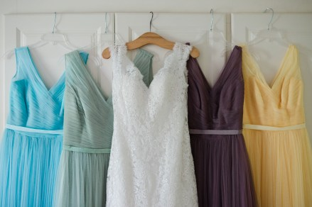wedding dress with pastel coloured bridesmaid dresses hanging on wardrobe