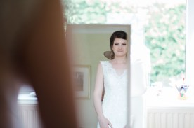 bride looks at herself in mirror after getting into wedding dress