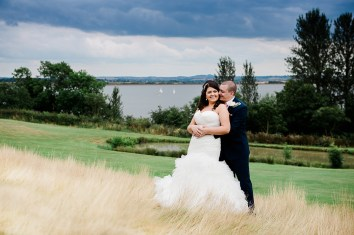 Bride and Groom Embrace with Draycote Waters Behind