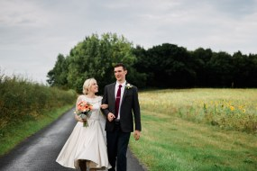 bride and groom walk down road swallows nest barn wedding photography