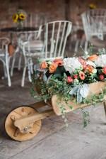 Flower filled wheelbarrel wedding barn decor
