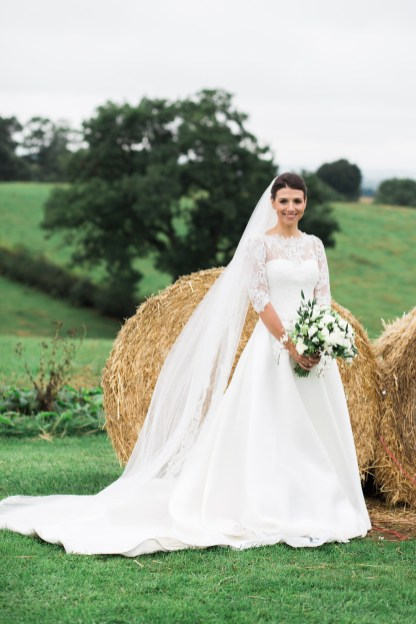 bride poses in front of hay bale