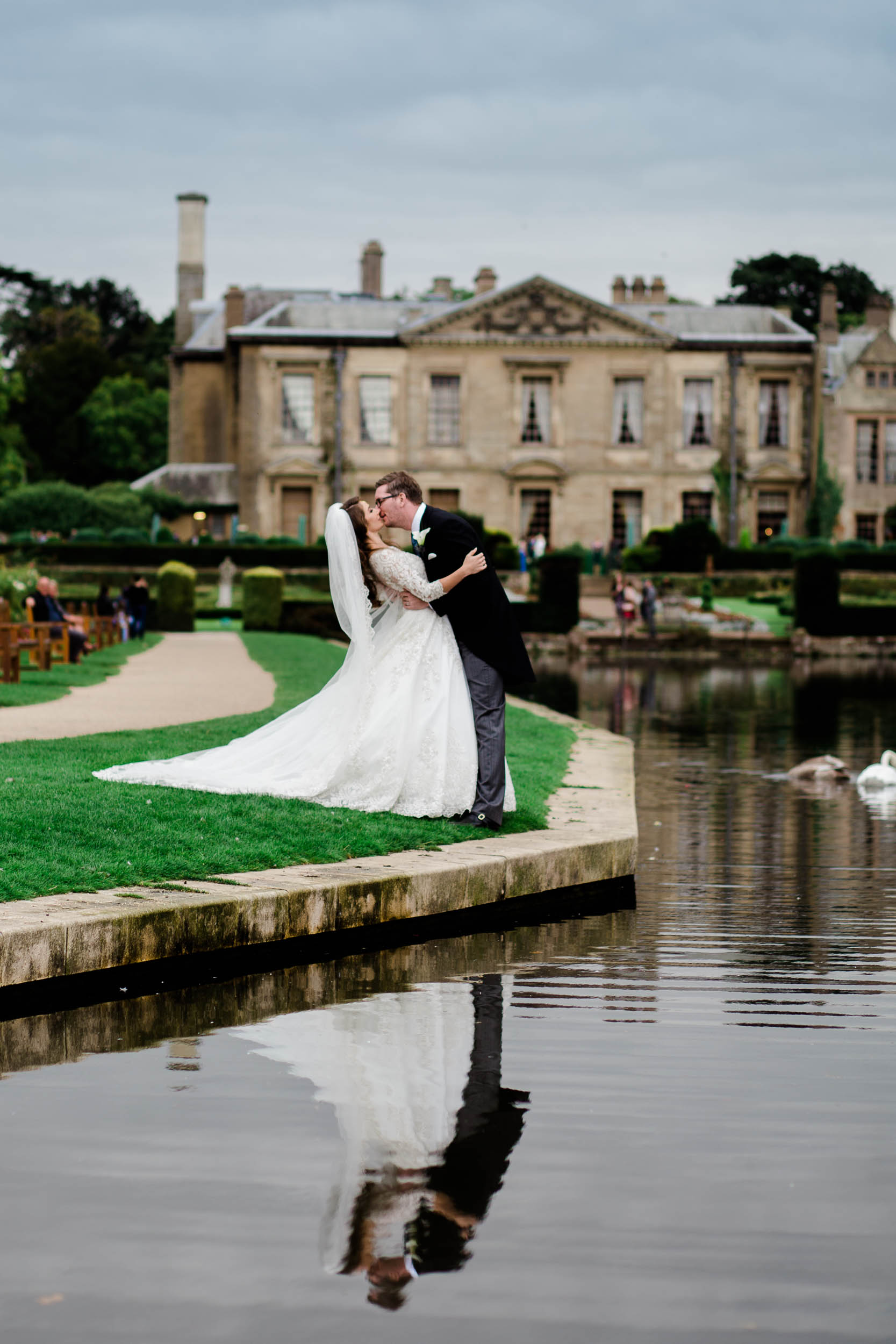 bride and groom kiss infront of coombe abbey