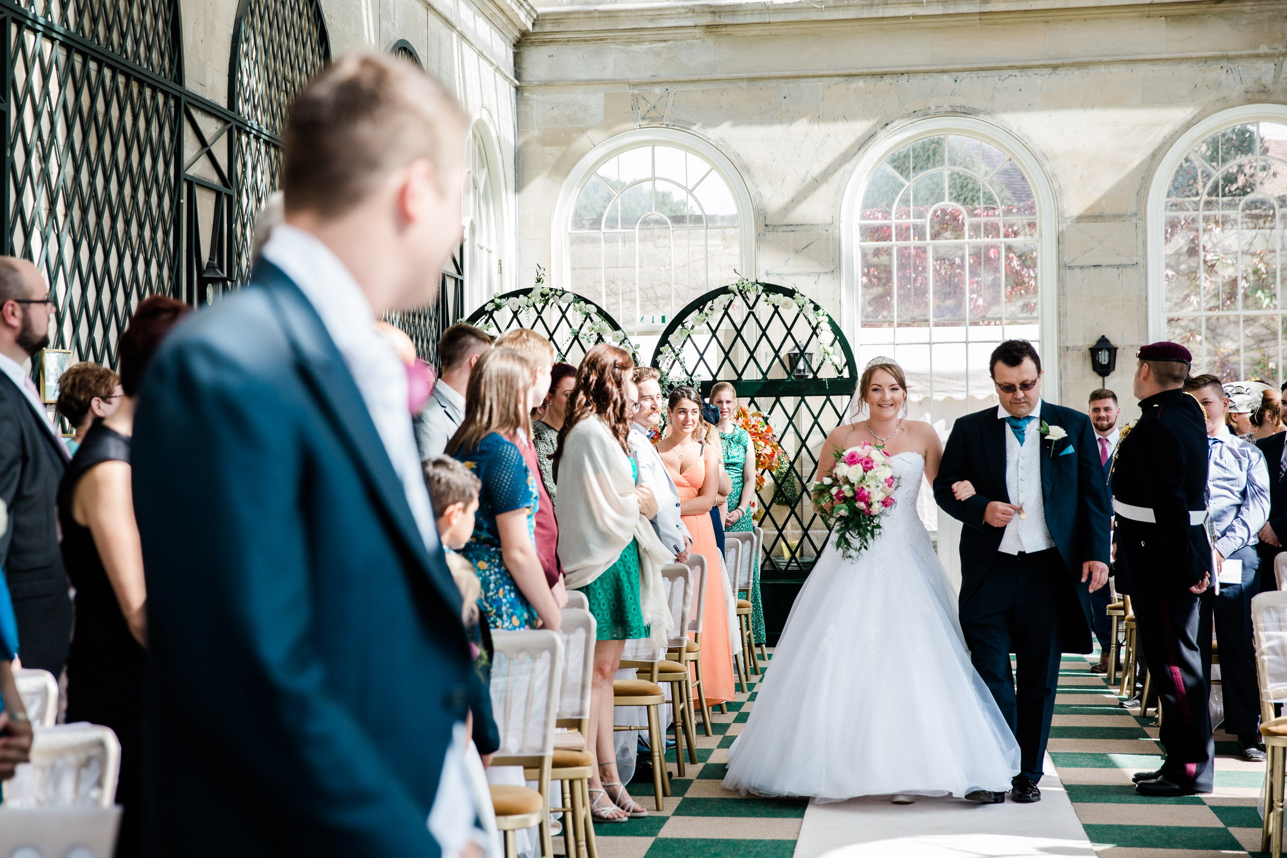 bride walks down the aisle or orangery at stoneleigh abbey