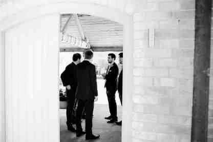 groom and groomsmen talking through doorway documentary style photography