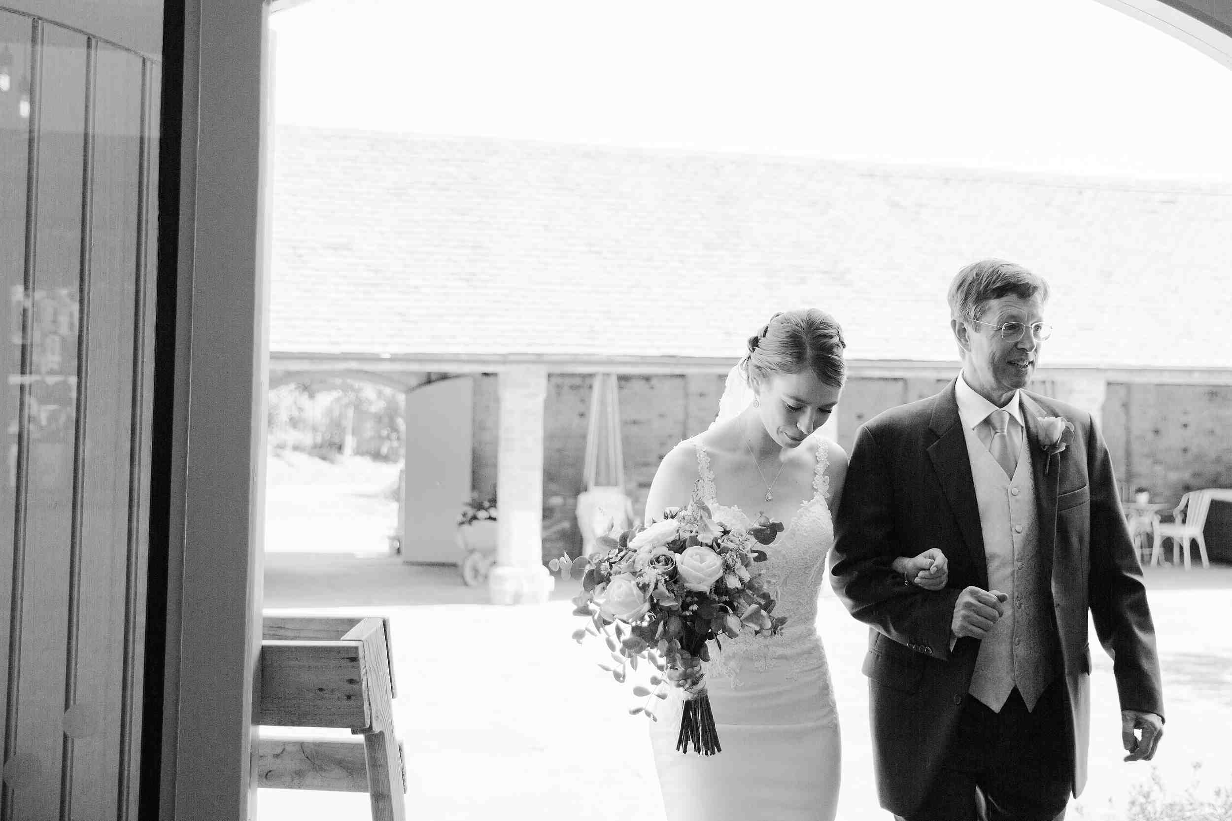 bride and father approach the ceremony arm in arm swallows nest barn