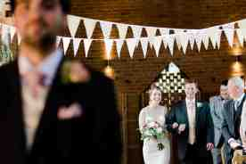 bride walks down aisle swallows nest barn