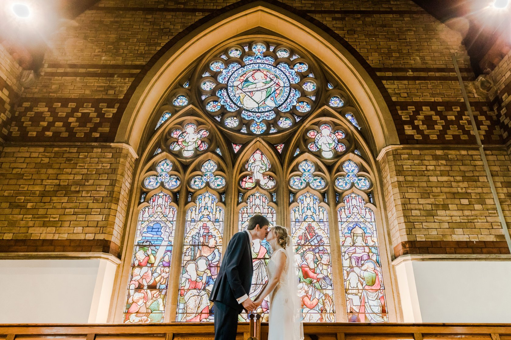 Bride Groom Kiss in front of Church Window St Pauls Church Leamington Spa Natural Wedding Photography Leamington Spa Relaxed Church Wedding
