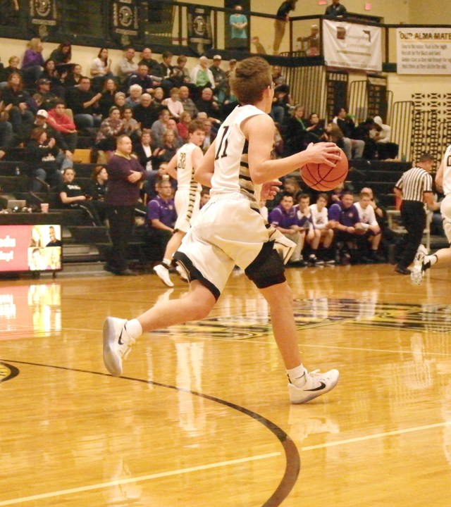 Perrysburg's point guard Griffen Sattler dribbles the ball down the court.