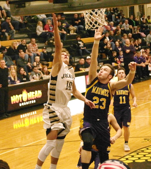 Perrysburg Senior Noah Walters makes a fast break layup avoiding Senior Maumee defender Hunter Thomasson.