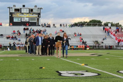 Students walk with parents on field