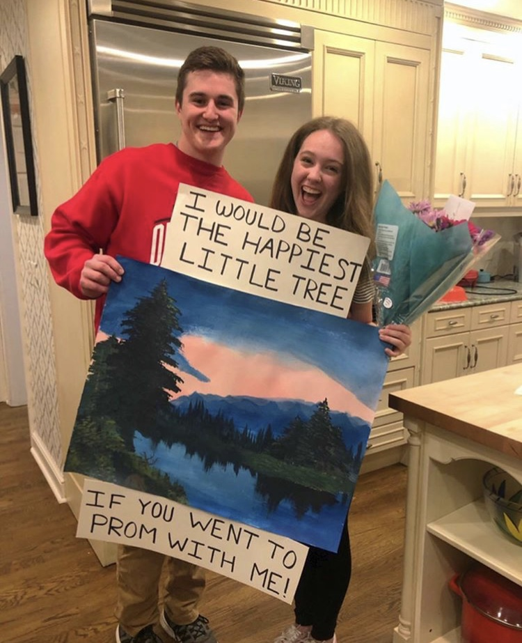 "A sign that says ""I would be the happiest little tree if you would go to prom with me"" above a Bob Ross painting"