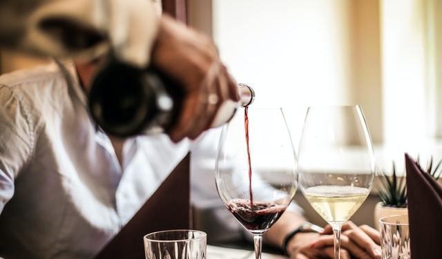 mano versa vino in un calice su un tavolo di un ristorante