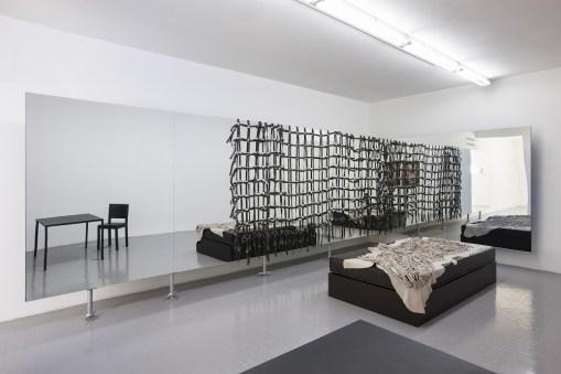 Monica Bonvicini, Black You, 2010, letto, tavolo, sedia, coperta di pelle, dimensioni ambientali e Straps & Mirror, 2010, 6 specchi, 14 tubi innocenti, cinghie di cuoio, specchi: 4 elementi da 200x150x2 cm, 1 elemento da 200x110x2 cm, 1elemento da 200x180x2 cm, cinghie di cuoio: 190x530 cm, veduta dell'installazione della terza sala Courtesy Galleria Massimo Minini, Brescia