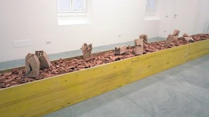 Loredana Longo, Piedediporco, 2017, cassa in legno, detriti, mattoni forati deformati dall'artista e cotti, cm 500x70x5: Courtesy Francesco Pantaleone, Milano