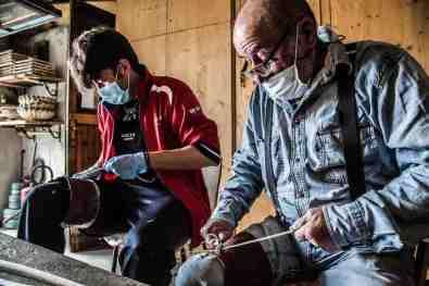 Artigiano e apprendista lavorano il legno di nocciolo