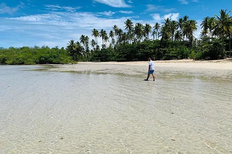 Eu caminhando nas águas transparentes da praia cercada por coqueiros