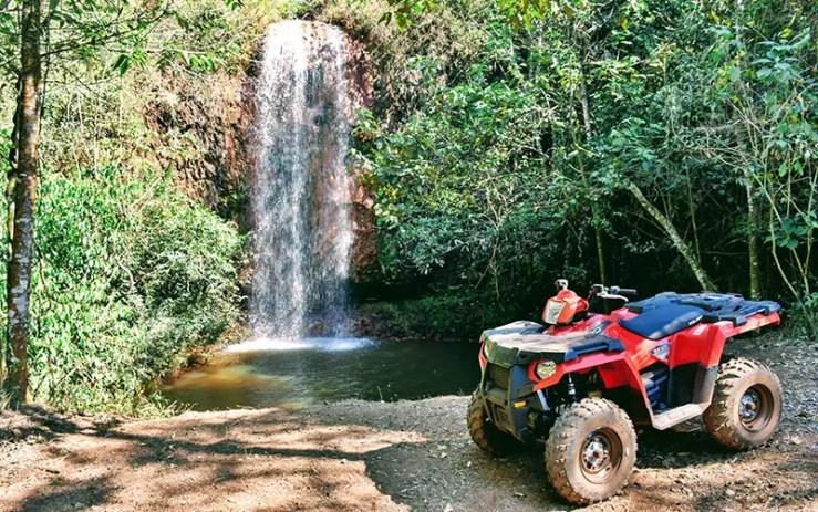 Passeio de quadriciclo em Brotas com cachoeira ao fundo (Foto: Divulgação)