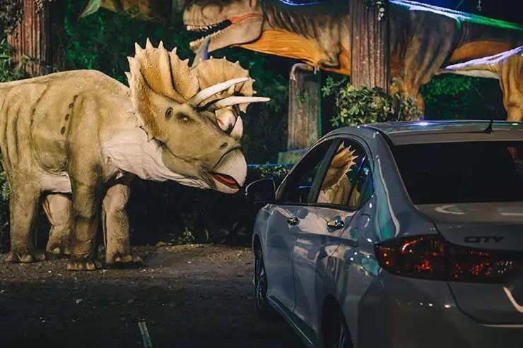Carro estacionado com dinossauros ao redor
