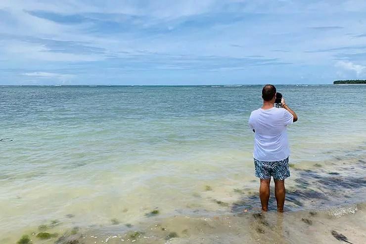 Rafael tirando foto no mar de Boipeba