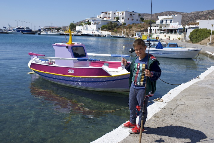 A young boy learns the art of fishing off the harbour