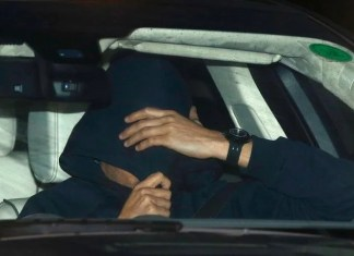 A man believed to be Jose Mourinho covers his face under a hoody as he is is driven out of Chelsea's training, in Cobham southern England