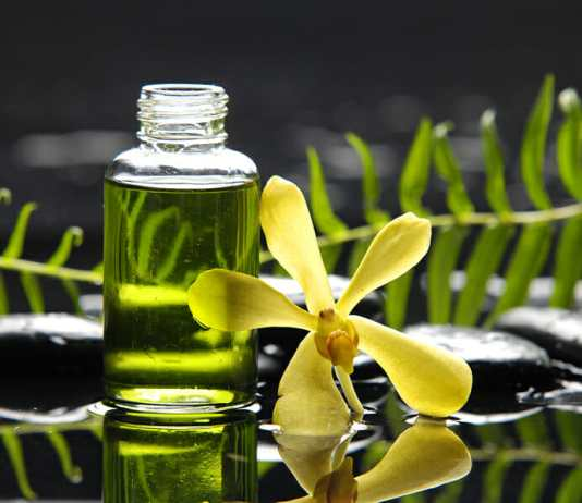 Massage oil and fern with yellow orchid reflection