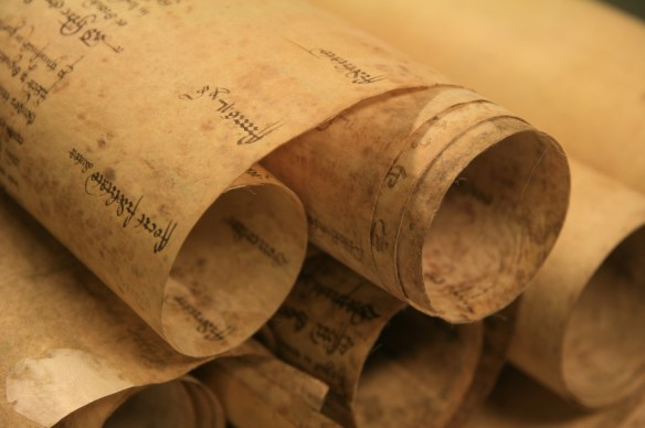 The earliest records are rolls made up of membranes of parchment stitched together at the top.  Although these records are cumbersome and unwieldy to use today, this was the quickest and easiest way to maintain a working accessible record