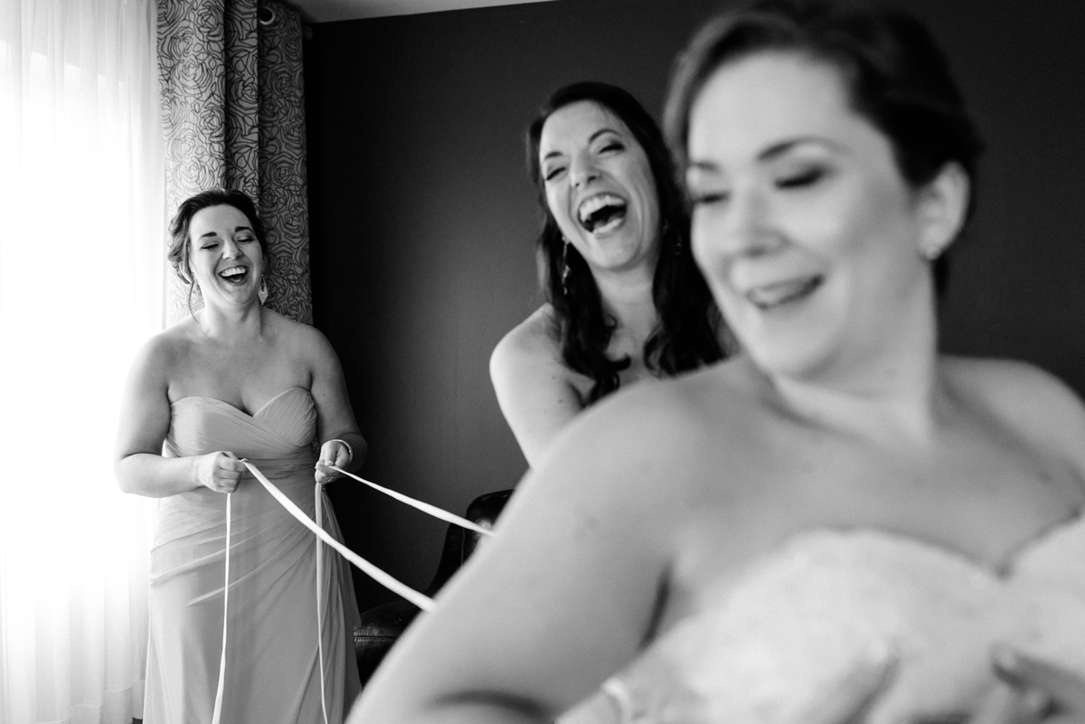 Candid wedding photo of bridesmaids laughing as they lace up a corset-back wedding dress