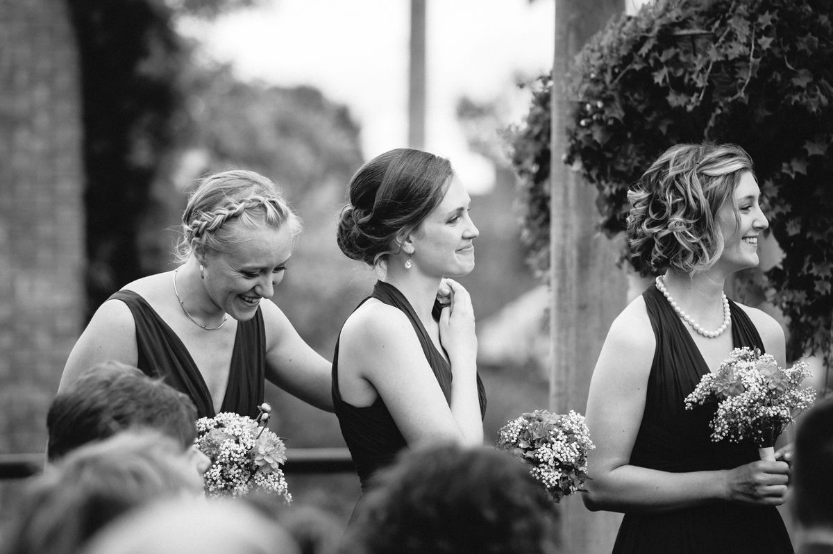 Black and white photo of bridesmaids' emotional reaction during a wedding ceremony at Chateau St-Ambroise, Montreal