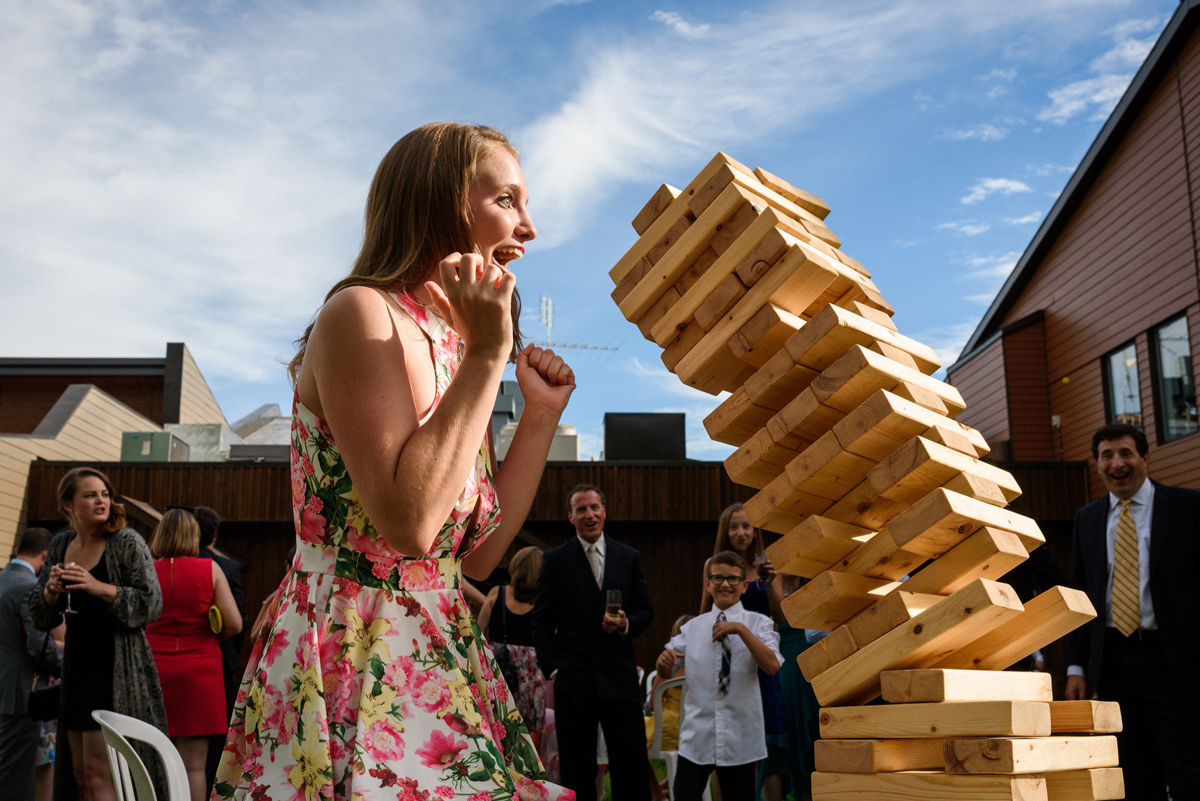In action wedding photo of giant JENGA tower collapsing during cocktail hour games