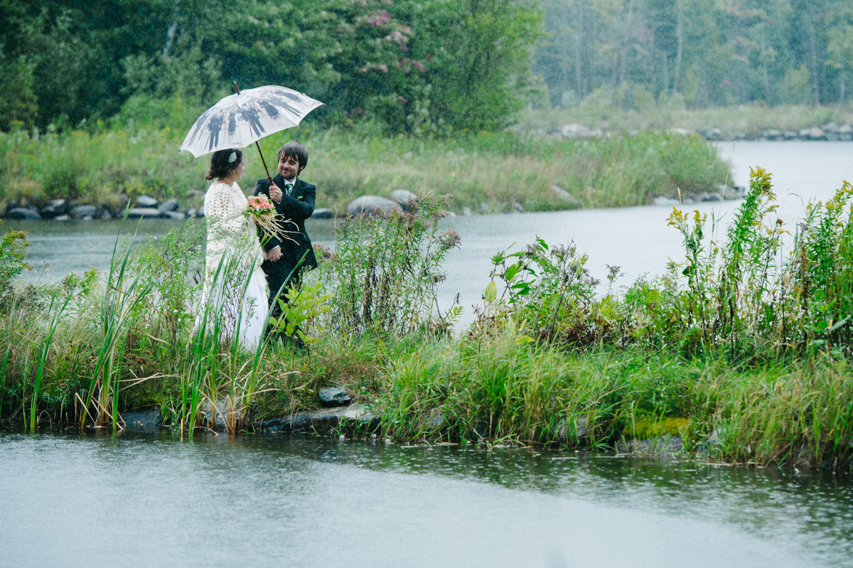 Rainy wedding photo with bride and groom walking under an umbrella
