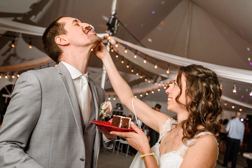 Bride feeding wedding cake to groom at wedding in Rougemont, Quebec