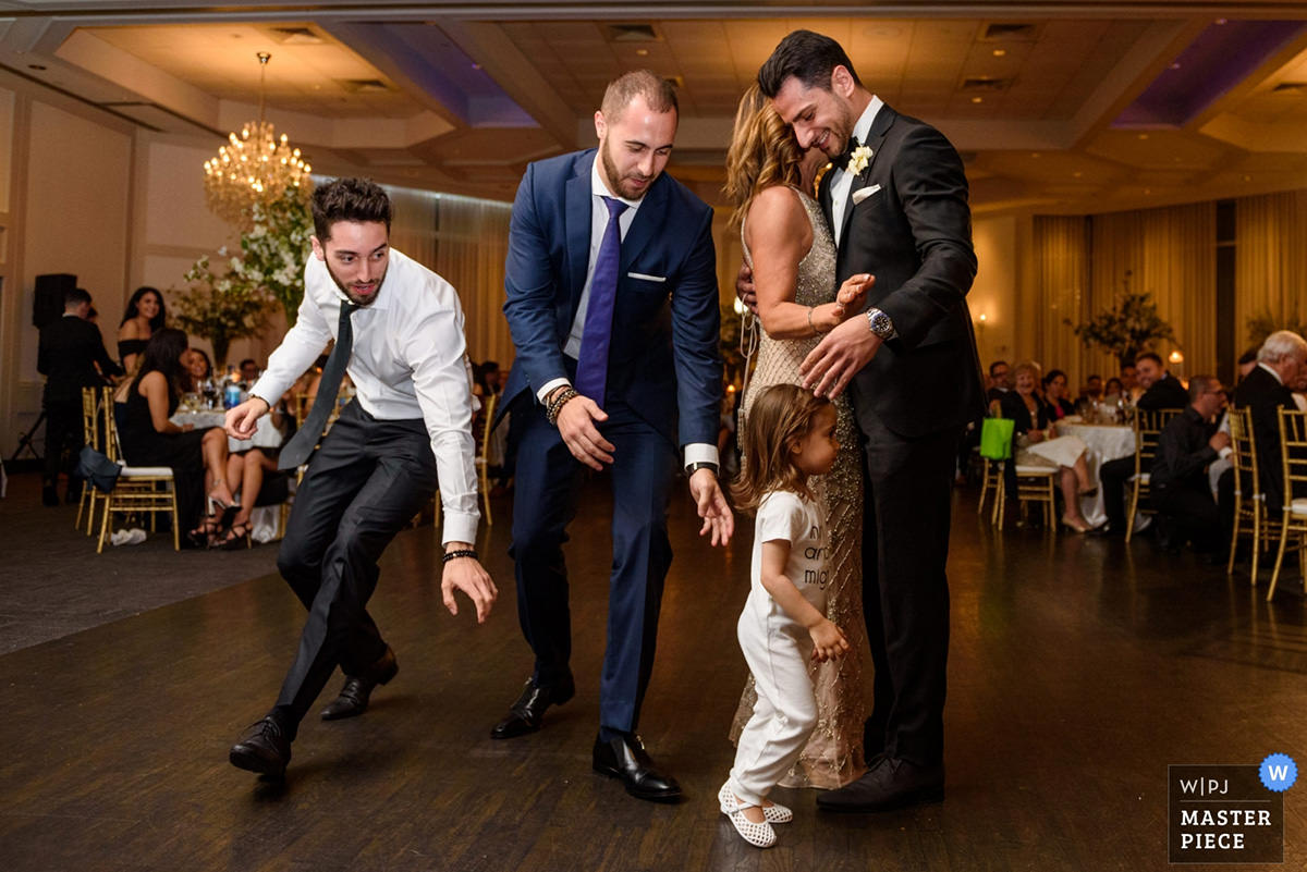 Award-winning wedding photo of father running after toddler