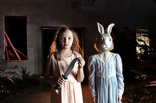 two small girls, one wearing a mask, the other holding a toy knife