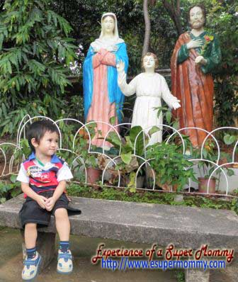 filipino toddler with the holy family statue
