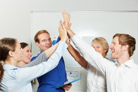 Business Team gibt sich High Five im Bro