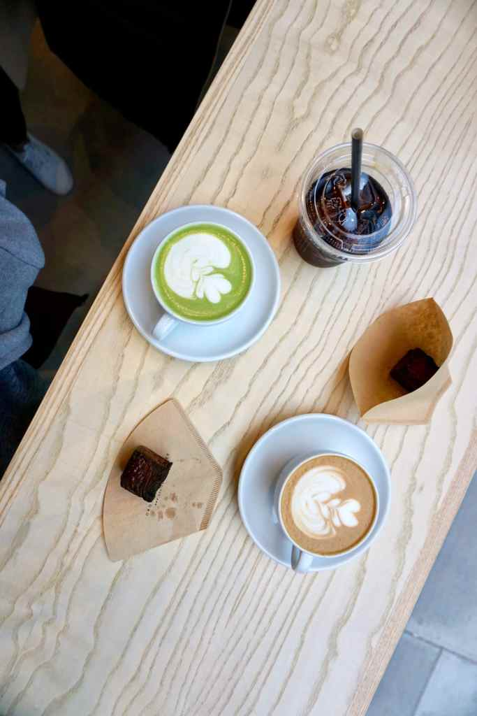 Image of a cup of Omotesando Koffee matcha latte, a cup of latte, and kashi pastries