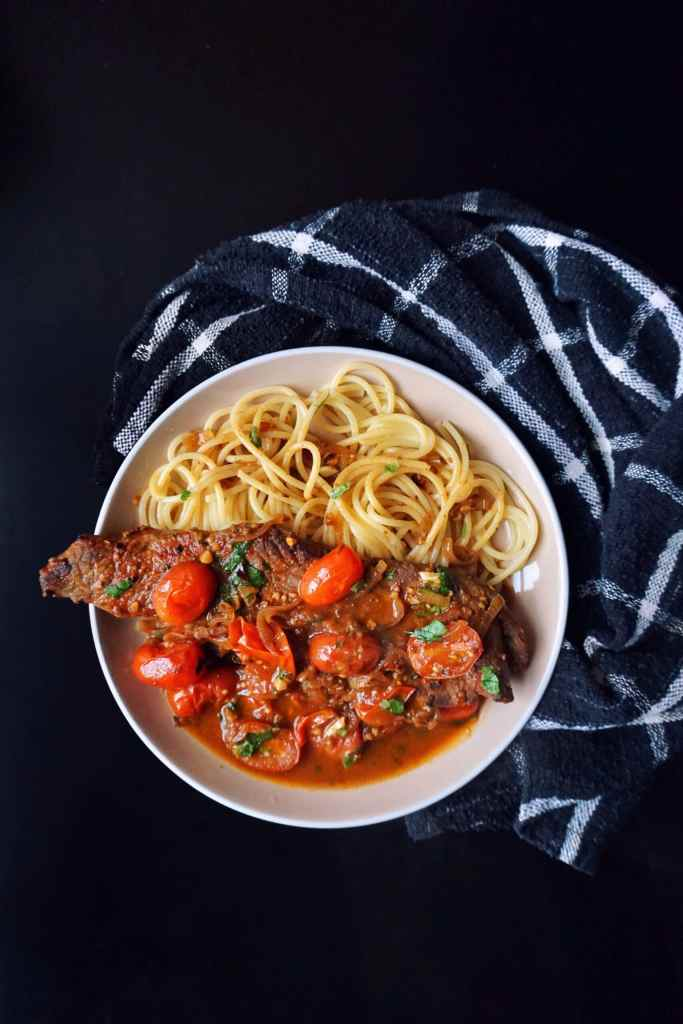 Image of a plate of steak with tomato sauce served with a side of spaghetti
