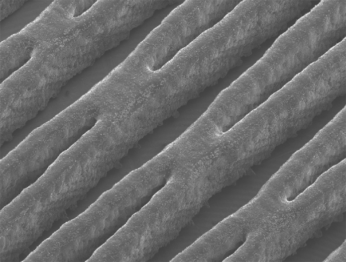 3D-printed polymer channel walls (raised). The liquid electrolyte flows in the recesses. The enlarged image shows a 3 x 4 millimetre section. (Photograph: Marschewski et al. Energy and Environmental Science 2017)