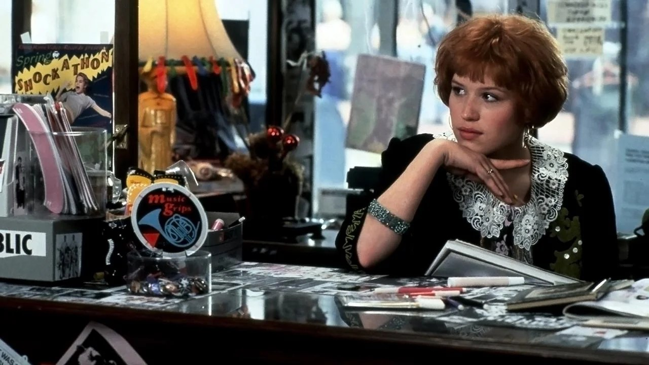 Molly Ringwald in Pretty in Pink (1986). Andie, wearing a black dress with short puffy sleeves and a white lacy collar, is sitting behind a cluttered store counter reading, her attention has been caught by something off camera.