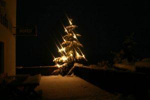 albero di natale con luci e neve
