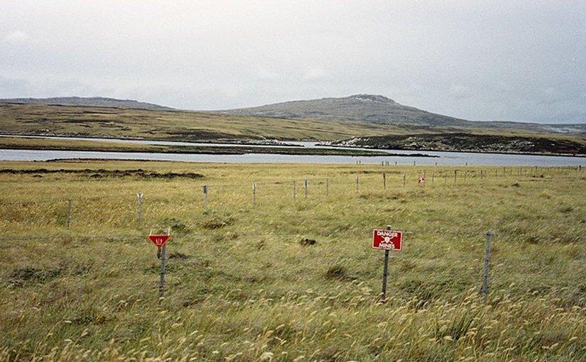 Although some minefields have been cleared, a substantial number of them still exist in the islands, such as this one at Port William on East Falkland. Photo by Apcbg, Wikipedia Commons.