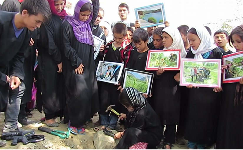 Sakina breaks a toy gun before burying it. Inam and other street kids await their turn.