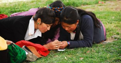 Tibetan women checking their cell phones. Photo by Tito Craige.