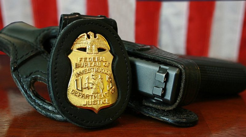 FBI badge and gun. Source: Wikipedia Commons.