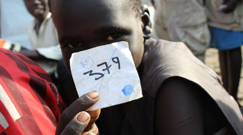In March 2015, a boy holds his registration number following a ceremony formalizing his release from the South Sudan Democratic Army (SSDA) Cobra Faction, in Lekuangole village, in Jonglei State. UNICEF/UNI181538/McKeever