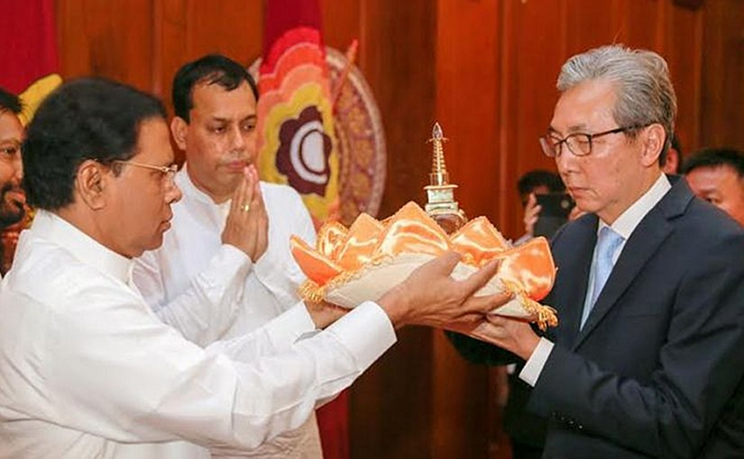 Sri Lanka President Maithripala Sirisena offers sacred Buddhist relics to the Deputy Prime Minister of Thailand Somkid Jatusripitak. Photo Credit: Sri Lanka government.