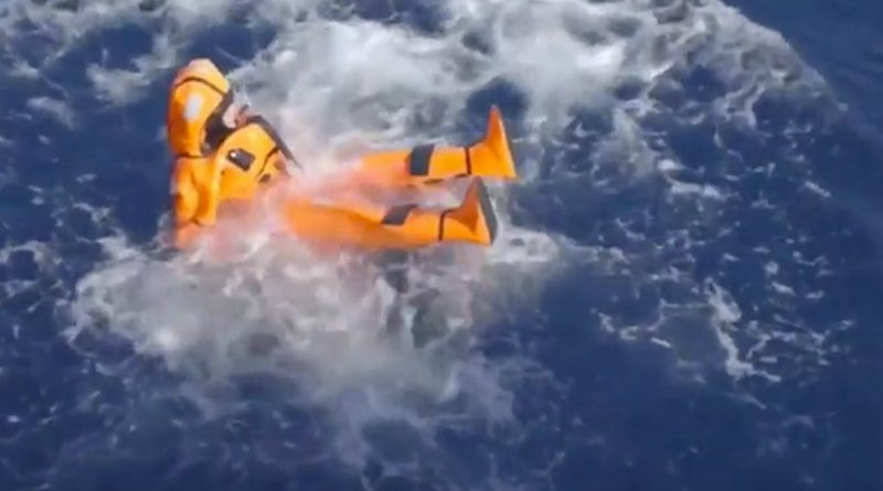 Norway's Minister of Migration and Integration Sylvi Listhaug jumps in the Mediterranean Sea in an orange survival suit.
