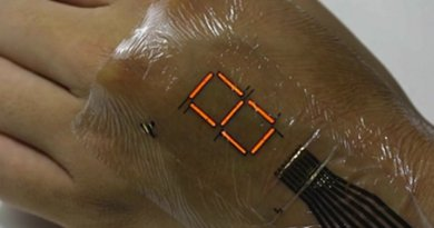 The red seven-segment PLED display in operation on the back of a hand. Credit: Someya Laboratory